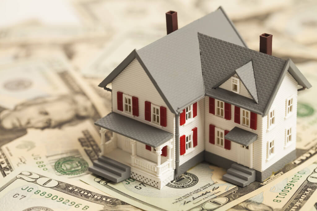 maqueta de una casa encima de billetes