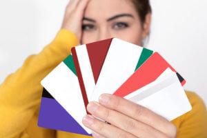 mujer sosteniendo muchas tarjetas de crédito