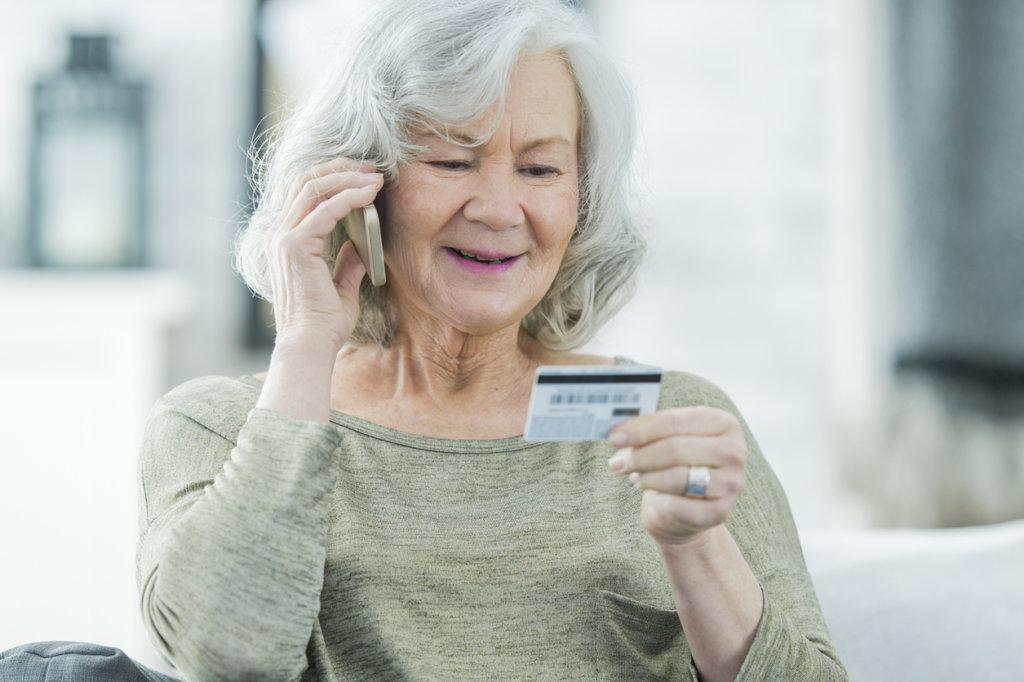 mujer hablando por telefono sobre su tarjeta de crédito