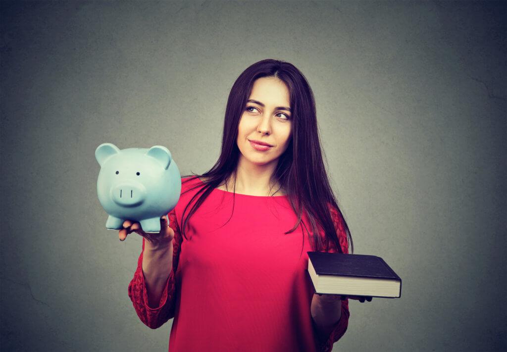 mujer con alcancía y libro an ambas manos