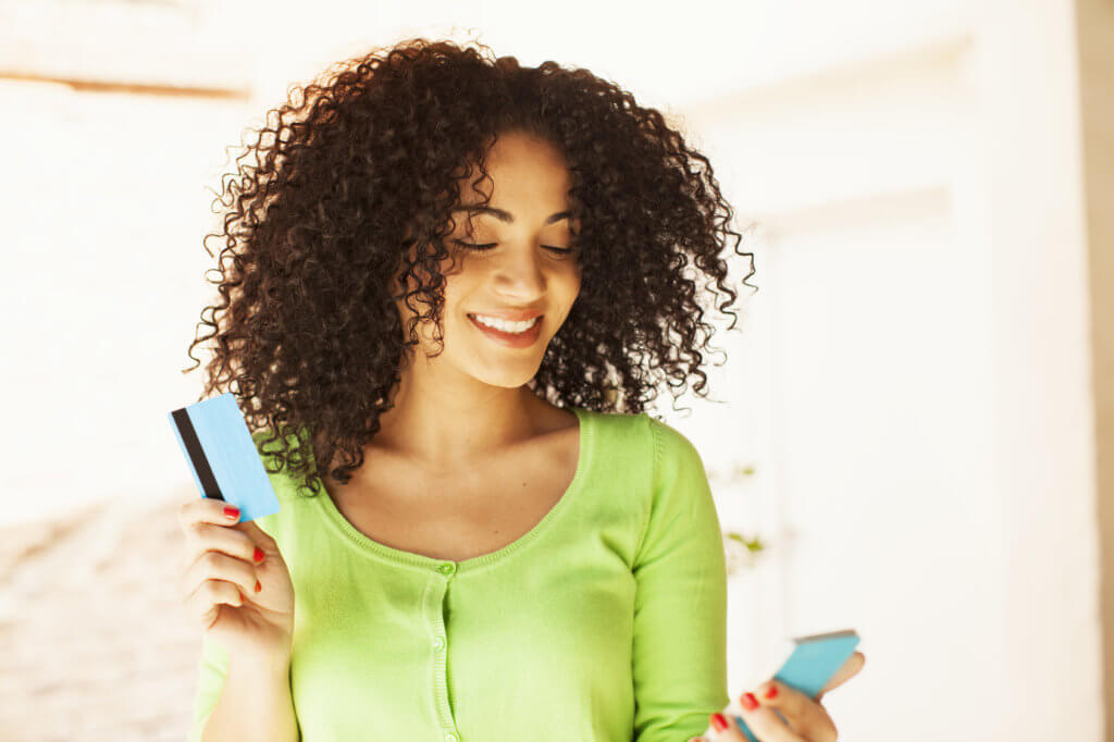 African american woman shopping with credit card and mobile phone