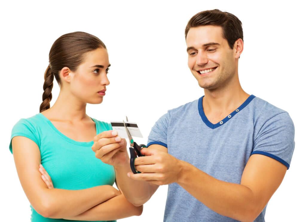 Serious Woman Looking At Man Cutting Credit Card