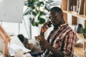 hombre hablando por teléfono sobre su tarjeta de crédito
