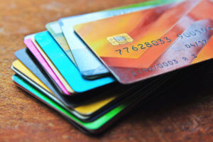 Big stack of multicolored credit cards on a wooden background