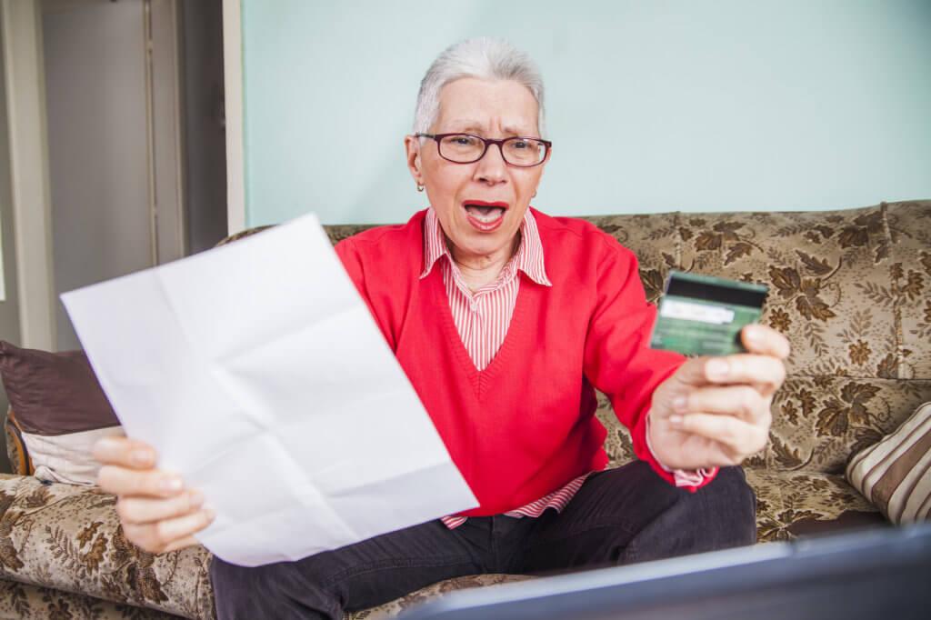 mujer asustada por informe de tarjeta de crédito