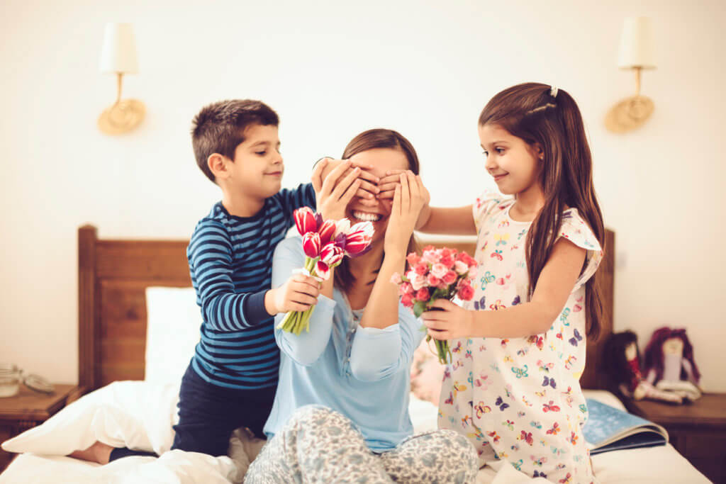 Mamá con dos hijos en la cama