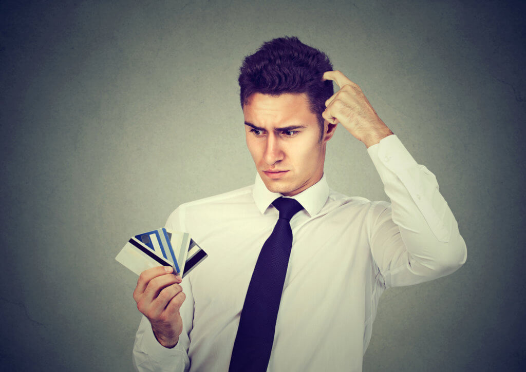 joven curioso con tarjetas de crédito a la mano