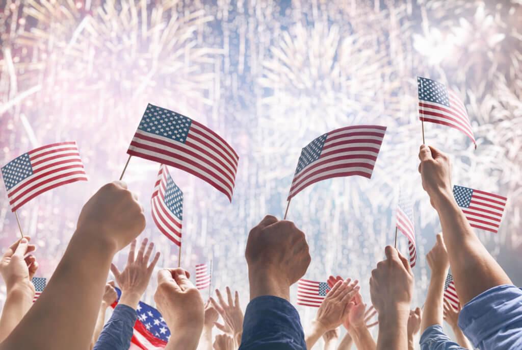 personas con banderas de Estados Unidos y fuegos artificiales