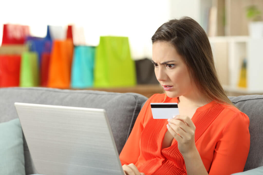 mujer revisando su tarjeta de crédito en la laptop