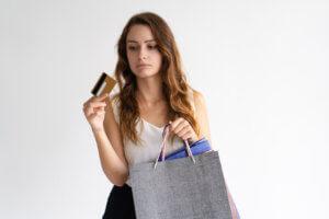 mujer con tarjetas de crédito de recompensas y bolsas en la mano