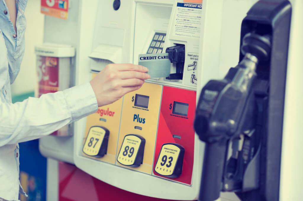 mujer pagando gasolina con tarjeta de crédito