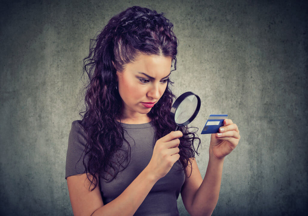 mujer viendo detalladamente su tarjeta de cargo
