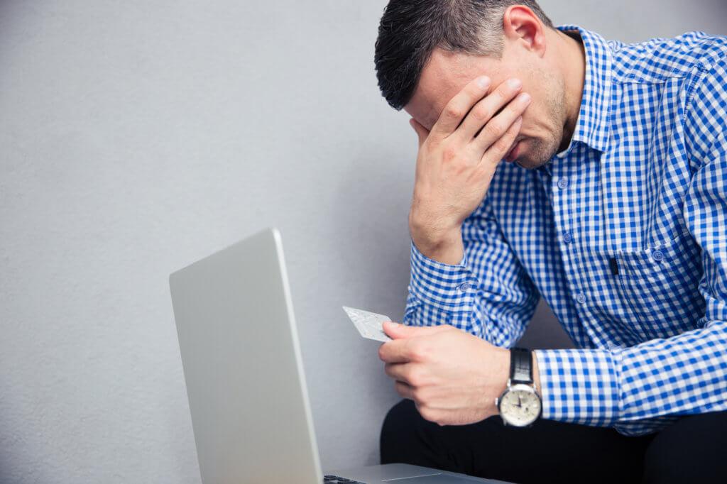 hombre preocupado por su deuda de tarjeta de crédito
