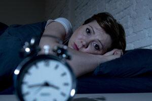 Mujer que no puede ormir por el estrés de la deuda