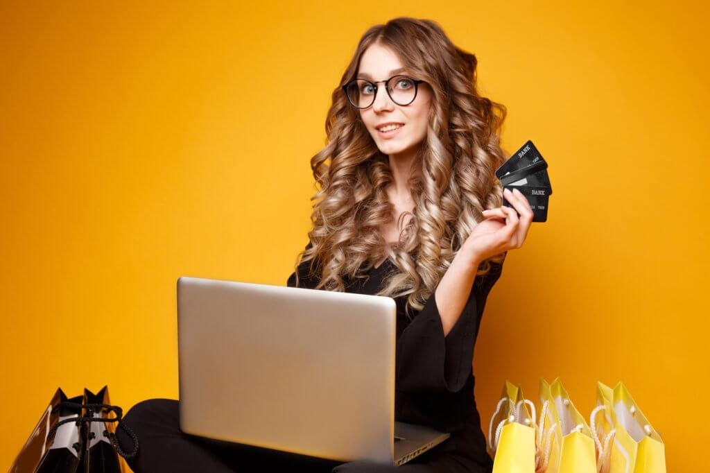 Mujer con laptop y tarjetas de crédito