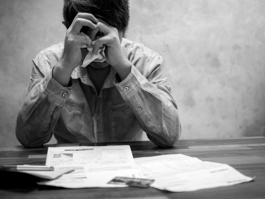 Hombre pensando en la deuda de tarjetas de créedito de su esposa