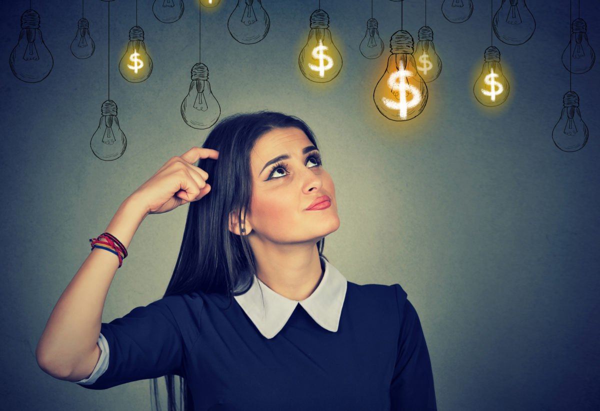 Thinking young woman looking up at dollar idea light bulbs above head