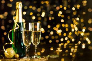 Copas con champaña rodeadas de decoración dorada en víspera de Año Nuevo