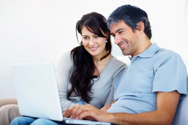 Hispanic couple looks at laptop