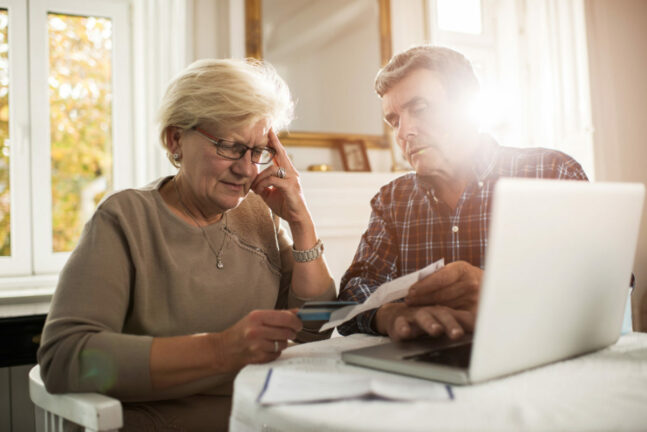 Older couple reviews credit card statements in front of computer