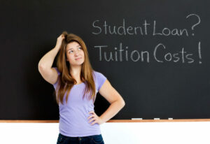 Woman contemplates blackboard: Student Loan? Tuition Costs! Why do women hold more student debt?