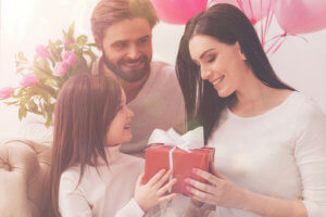 Father and daughter give Mom gifts for Mother's Day 2018