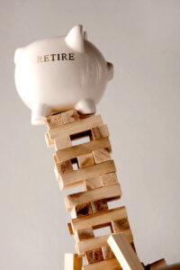 Fear of outliving your retirement savings: people worry their retirement savings won't stand up as symbolized by a piggy bank on a Jenga tower