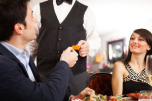 Man paying dinner in a restaurant with a rewards credit card