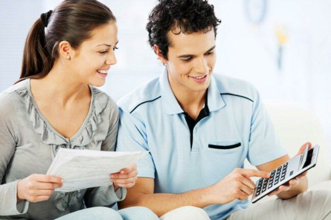 how to build credit; young woman looking at papers, young man with calculator