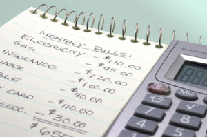 how to live debt free; calculator and notepad with budget written on it