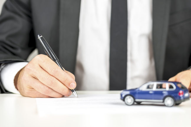 how to build credit; Closeup of man signing a contract of car sale