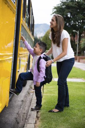 back to school shopping; mom helping kid onto school bus