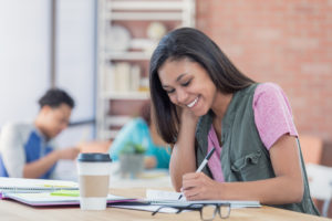 women and money, school; Cheerful African American college girl smiles while studying the the library or student lounge.
