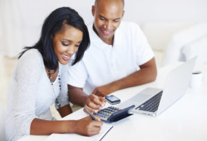 women and money, relationships; couple with calculator and computer reviewing finances