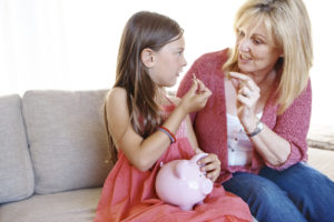 women and money, children; older woman talking about money with a little girl holding a piggy bank