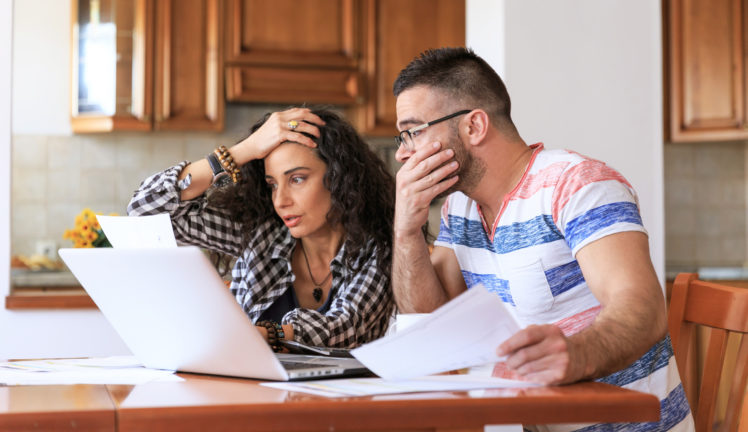 loans to family members; couple at kitchen table with bills looking stressed