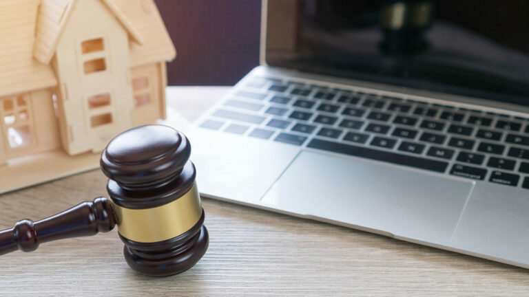 debt and divorce; computer, gavel, and mini house on a table