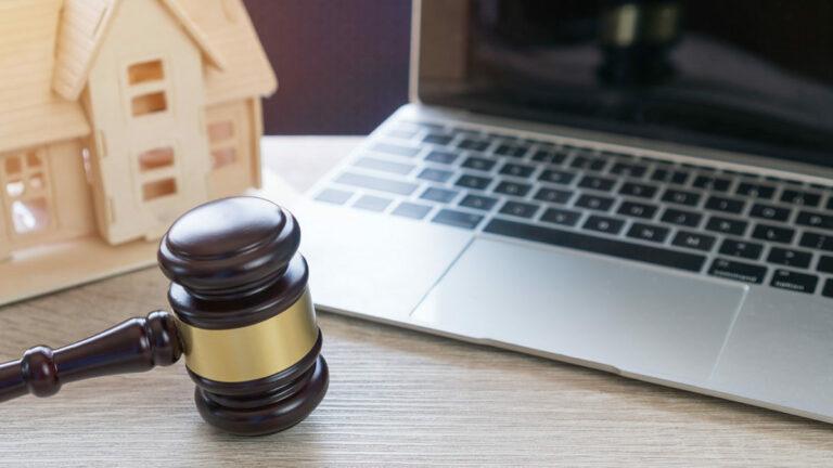 deuda y divorcio; computadora, y mini casa en una mesa