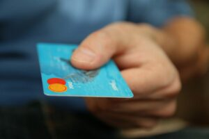 can i keep credit card reward points in after i consolidate my debt; person holding out blue credit card