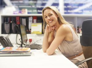 woman leaning on desk smiling at camera; smart goals
