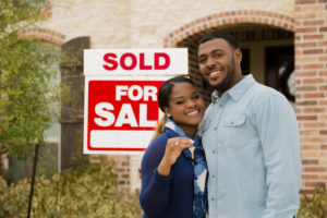 how do mortgages work?; Minority First Time Homebuyers standing in front of a sold house