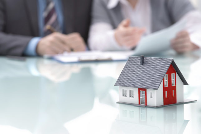 how do mortgages work?; Businessman signs contract behind home architectural model