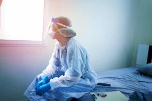 healthcare workers financial relief guide; doctor in PPE looking out a window