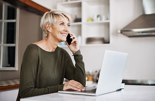 Baby boomer mother at home on the phone and her computer