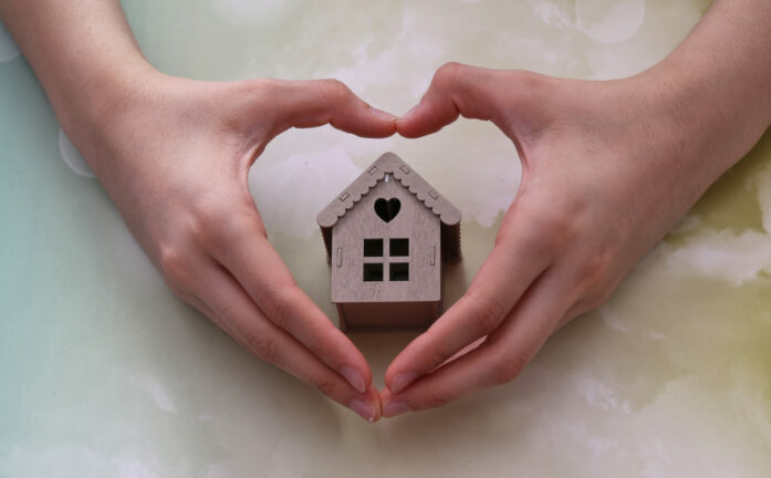 homeowners guide COVID-19; hands making a heart around a small cardboard house