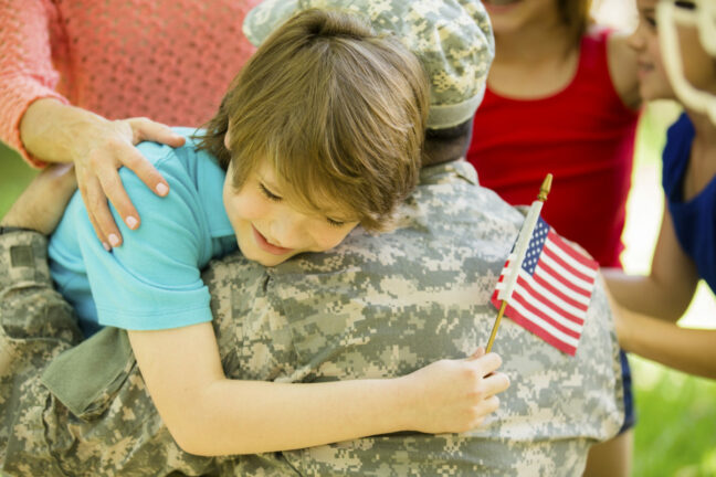 military identity theft; Service Member hugging a child holding an American flag