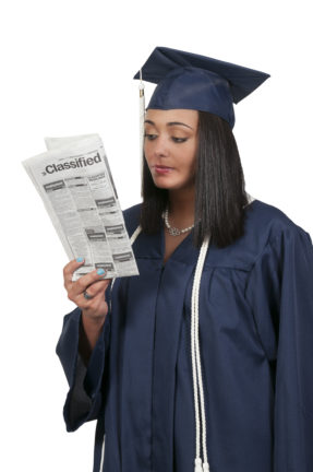 recession guide for grads; woman in cap and gown looking at newspaper classifieds section
