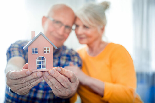 reverse mortgage COVID-19 coronavirus help; older couple holding out a miniature house
