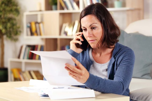 Middle aged woman reviewing her bills while talking on the phone