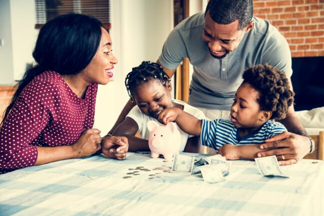money saving tips for families; man and woman with two young kids counting money with a piggy bank